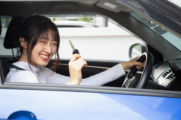 Young happy Asian car driver woman smiling and showing new car keys. Novice drivers concept