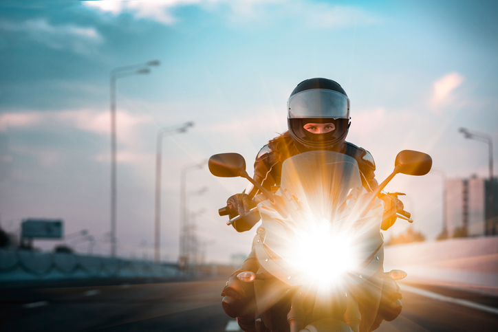 Woman drives on a motorcycle on a morning highwaymorocycklist racing on a morning city background