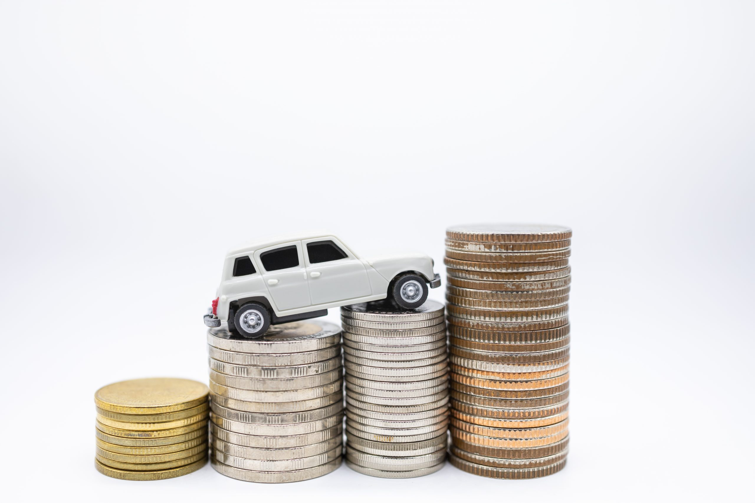 DirectAsia Insurance_white toy car on stacks of coins, tax