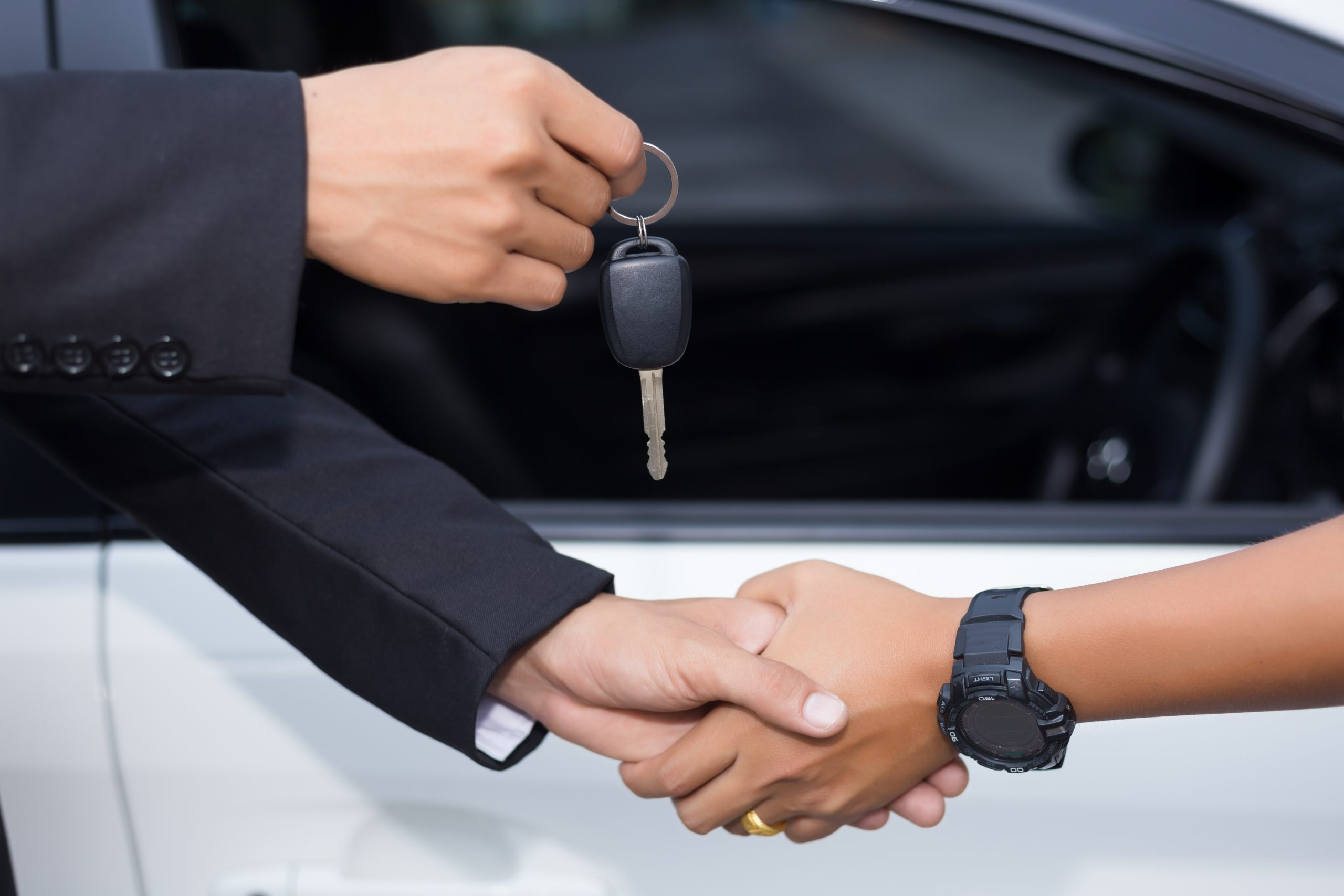 ar salesman handing over the key for a new car to a young businessman in front of the white car