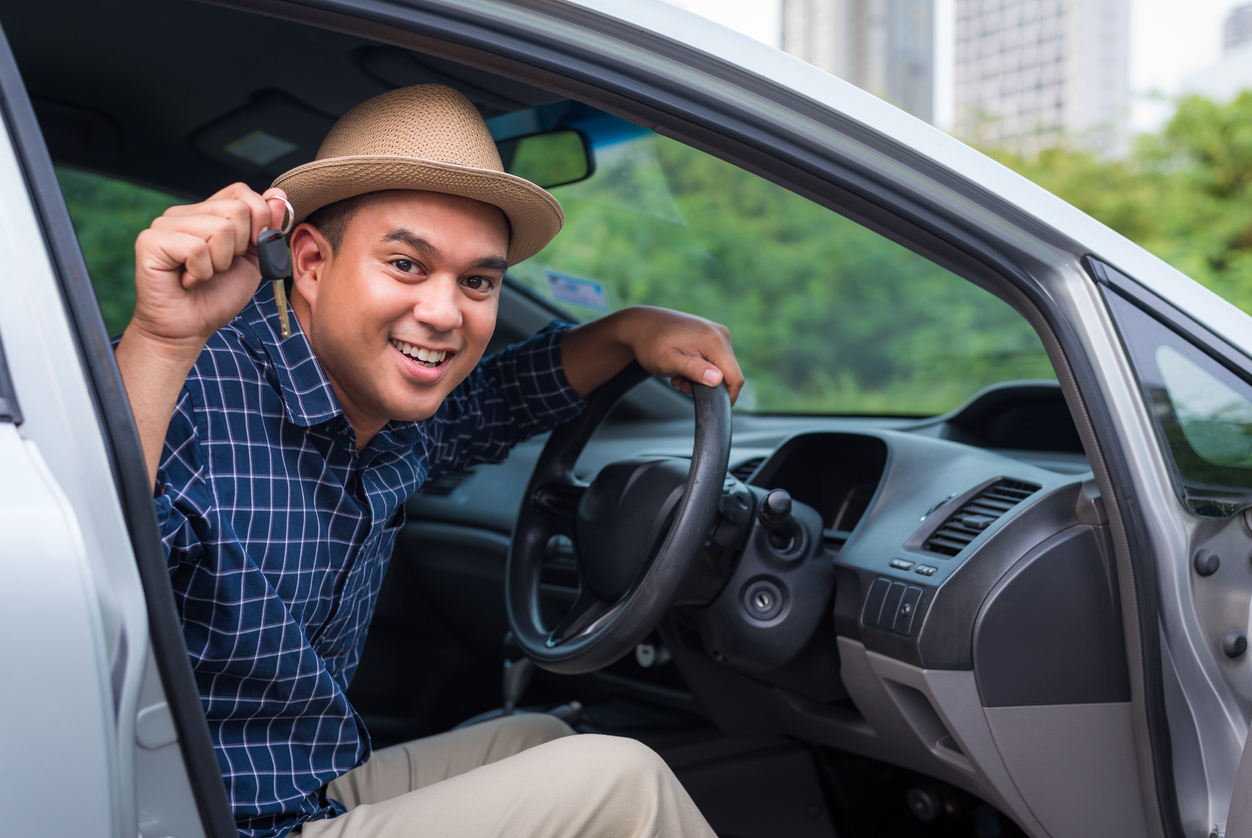 Asian man holding a car key for used car