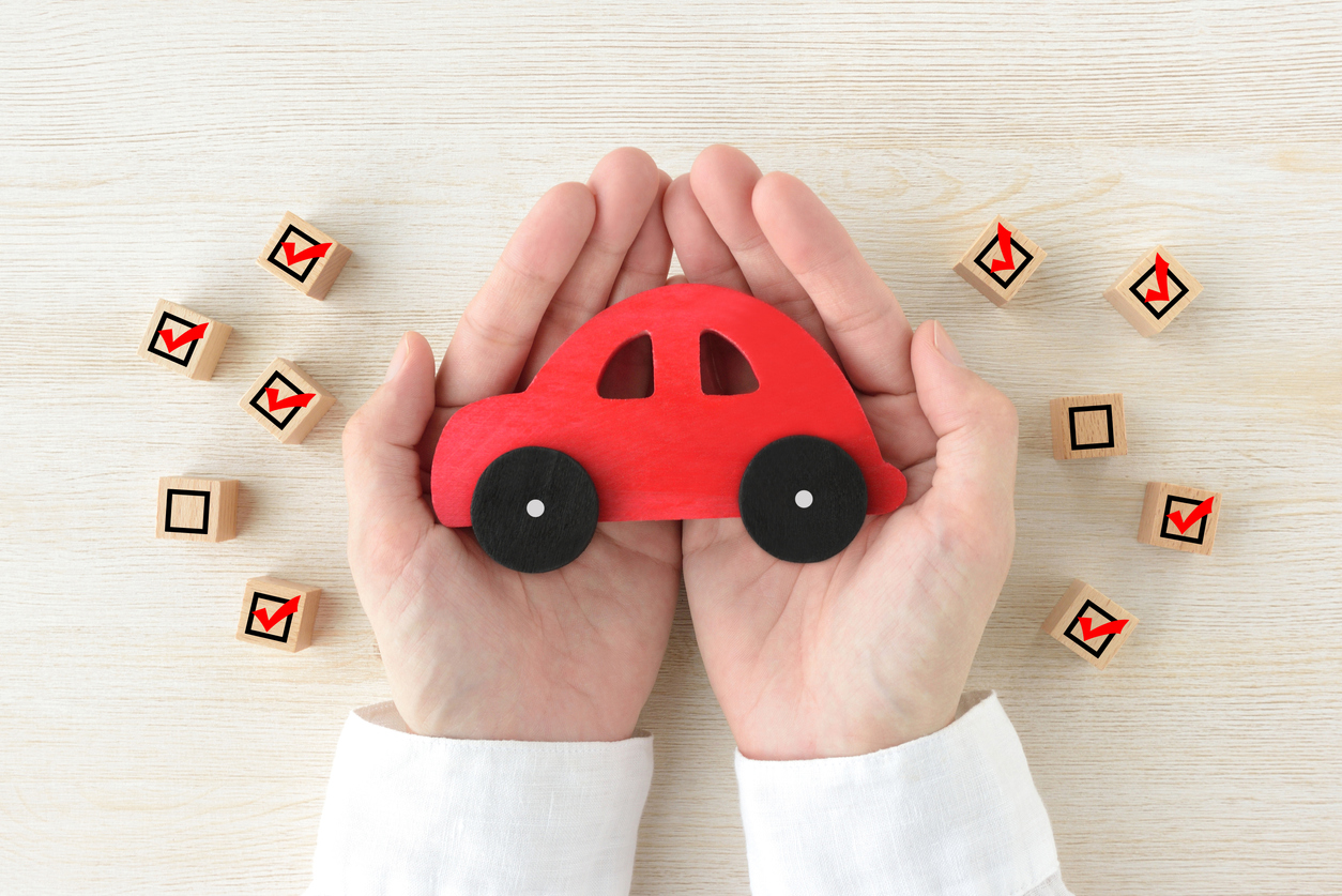 DirectAsia Insurance_Person holding a red car with several wooden checkbox cubes by the sides