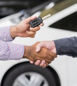 DirectAsia Insurance_Two men shaking hands with one holding on to a car key to handover to the other