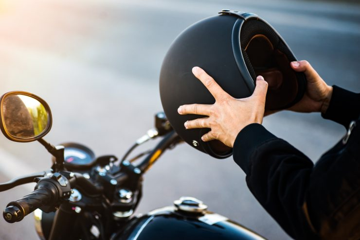DirectAsia Insurance_A person sitting on a motorcycle, holding the motorcycle helmet