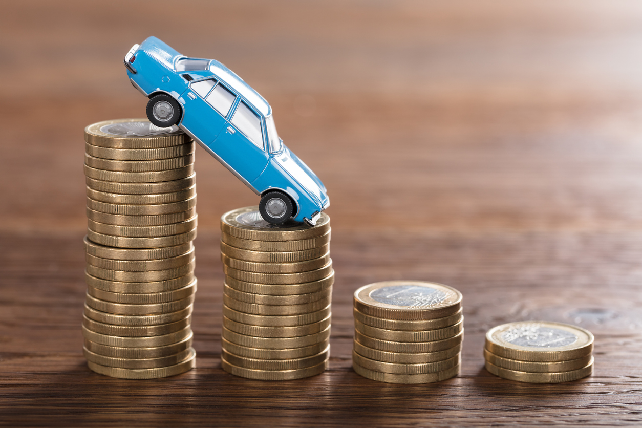 DirectAsia Insurance_A blue toy car going down stacks of coins in a downward slope
