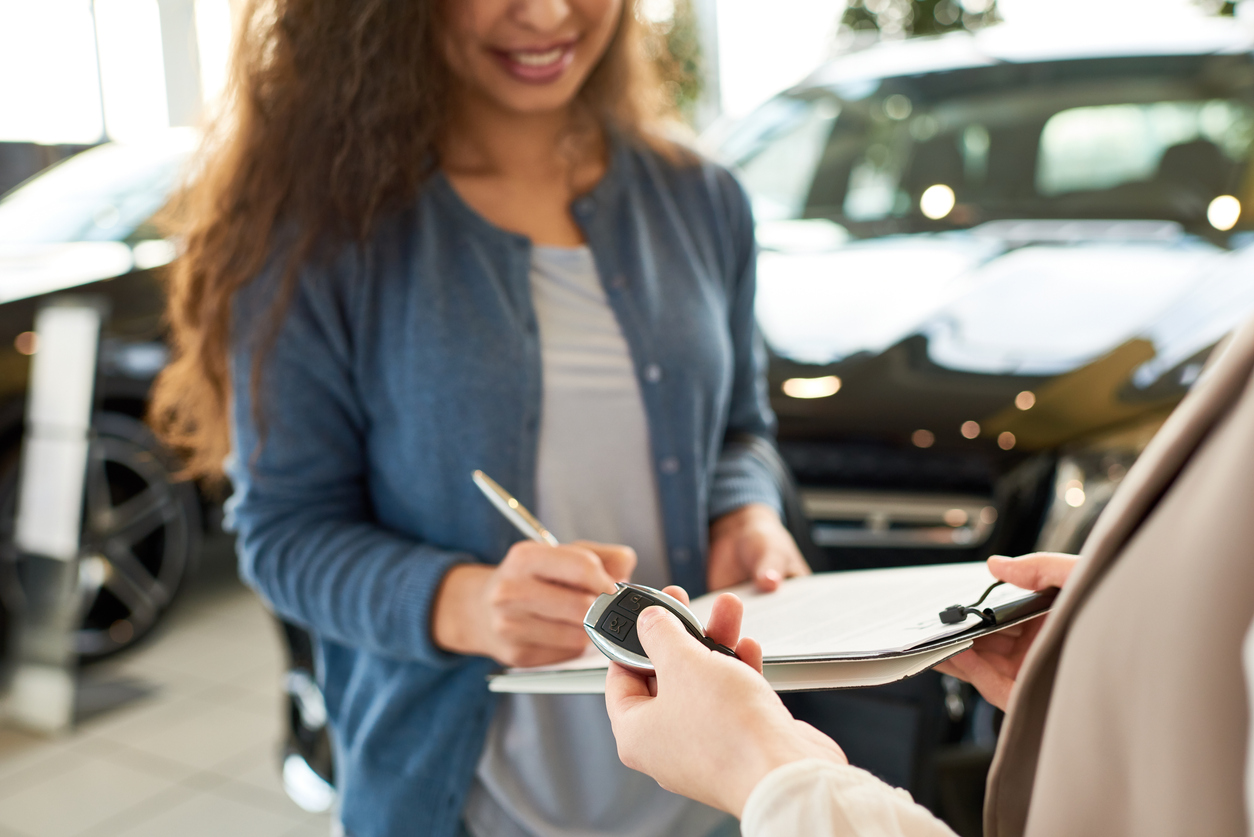 DirectAsia Insurance_A female holding a pen, signing papers and another person waiting to pass the car key to her