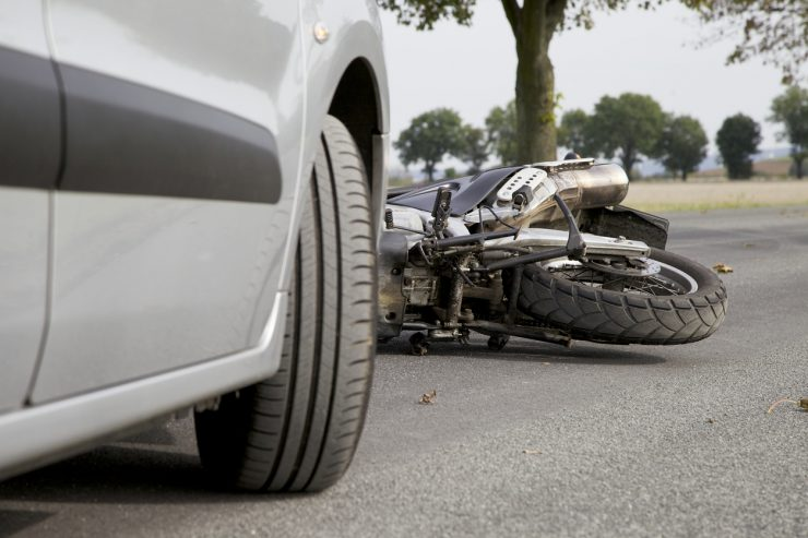 DirectAsia Insurance_a motorcycle lying on the road beside a car