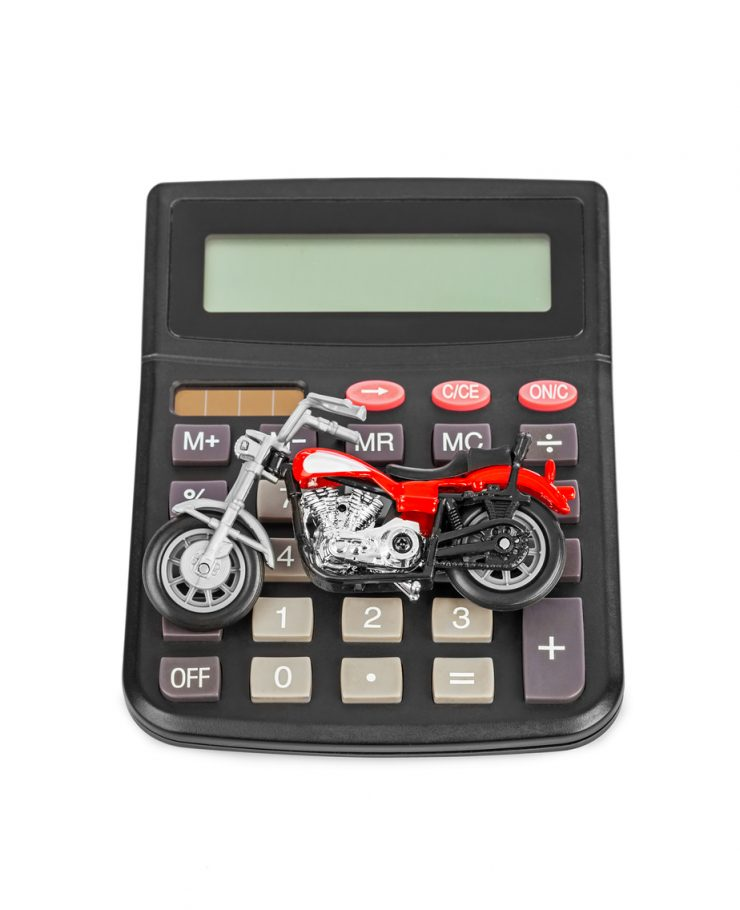DirectAsia Insurance_a metal motorcycle toy sitting on top of a calculator
