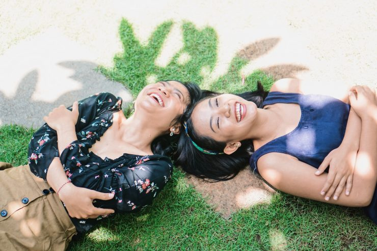 DirectAsia Insurance_Two females lying under a tree shade, smiling brightly on a sunny day