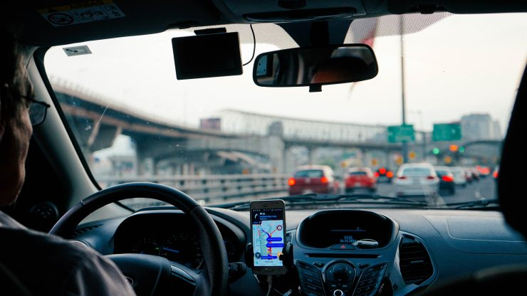 DirectAsia Insurance_Car driver using a GPS app on his phone on the road
